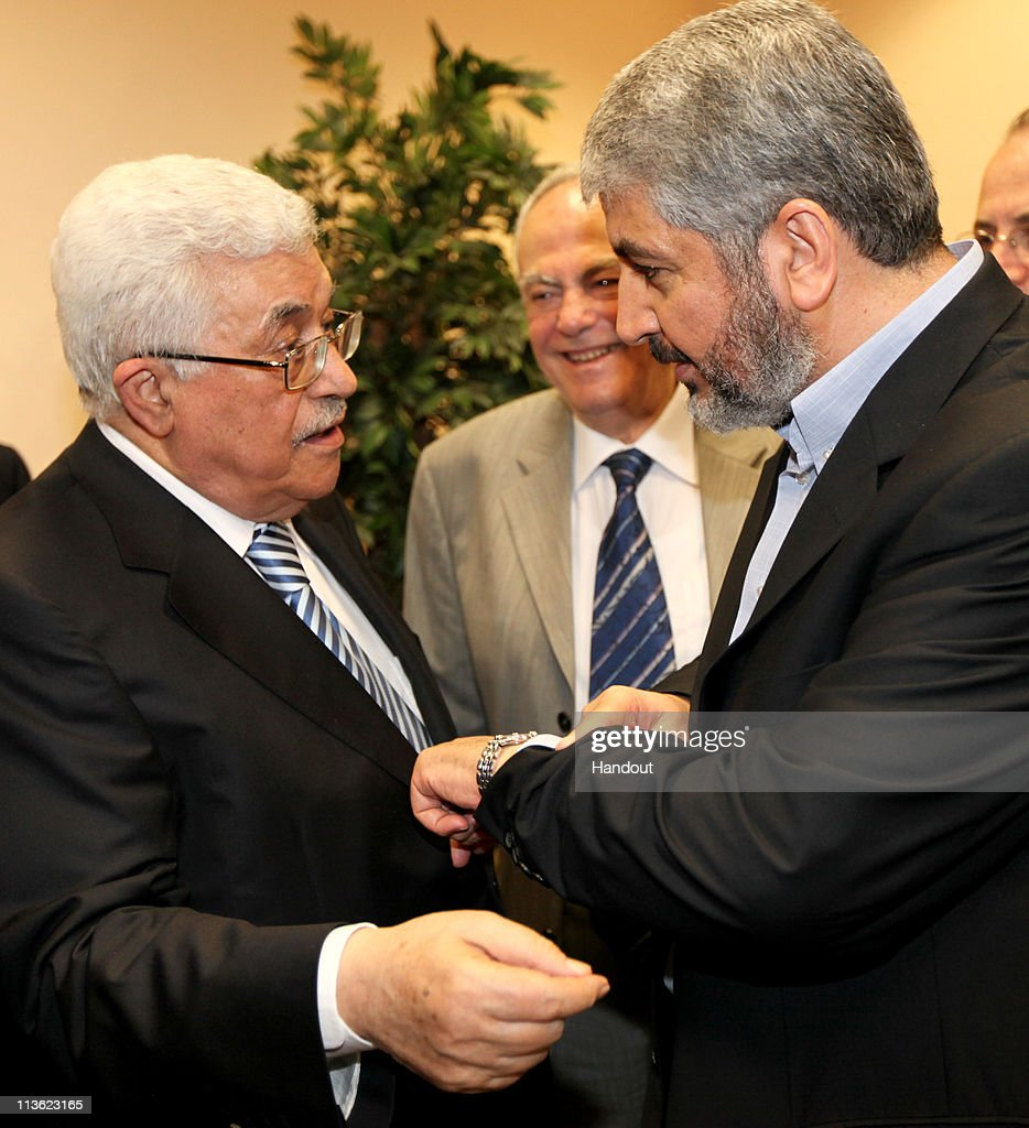 In this handout image provided by PPM, Exiled Leader of Hamas, Khaled Mashaal (R) meets with President of the Palestinian National Authority, Mahmoud Abbas (L) on May 4, 2011 in Cairo, Egypt. The rival factions, Fatah and Hamas, signed a reconciliation accord in Cairo after reaching common ground against Israeli occupation and peace efforts. Mashaal said they had a 'common goal; a Palestinian state with full sovereignty on the 1967 borders with Jerusalem as the capital'. Israeli Prime Minister Benjamin Netanyahu claimed that the reconcilation between the factions as a 'blow to peace', but the US declined to make any comment.