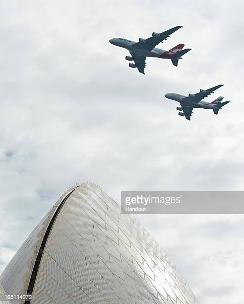 In this handout image provided by Qantas A Qantas Airbus A380 and Emirates Airbus A380 fly over Sydney Harbour on March 31 2013 in Sydney Australia...
