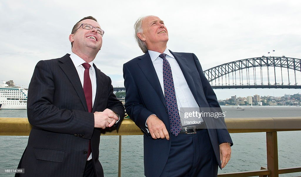 In this handout image provided by Qantas, Qantas CEO Alan Joyce (L) and Emirates President Tim Clark watch from the steps of the Sydney Opera House their respective Airbus A380s fly over Sydney Harbour on March 31, 2013 in Sydney, Australia. The two Airbus A380s display is believed to be the first of its kind between two seperate airlines to fly over Sydney's Harbour which will mark the alliance between the two airlines.
