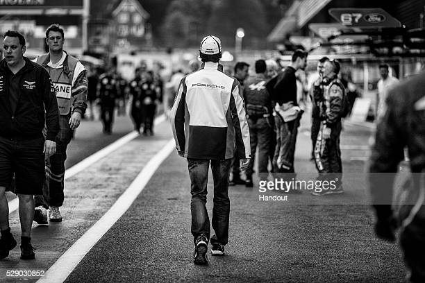 In this handout image provided by Red Bull #1 Porsche LMP1 car driver Mark Webber of Australia walks back through the pits after watching the...
