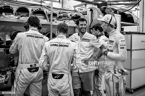 In this handout image provided by Red Bull #1 Porsche LMP1 car driver Mark Webber of Australia reacts while talking with team mates Brendon Hartley...