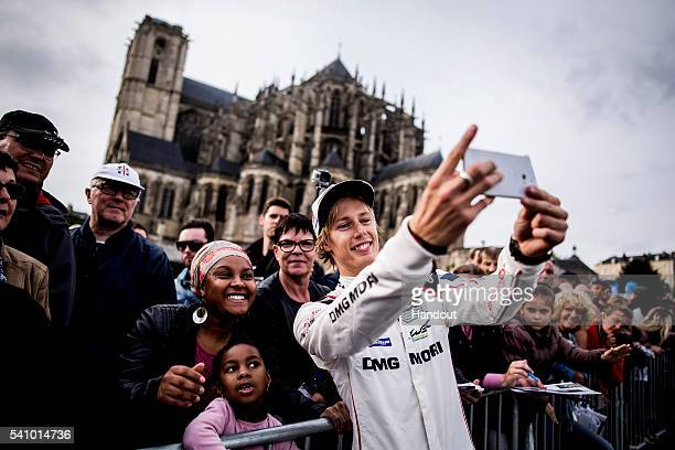 In this handout image provided by Red Bull #1 Porsche LMP1 driver Brendon Hartley of New Zealand takes a selfie with a spectators phone during the...