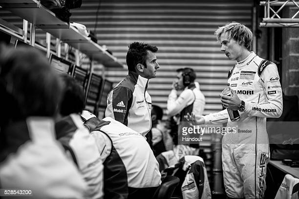 In this handout image provided by Red Bull #2 Porsche LMP1 car driver Roma Dumas of France in discussion with Porsche LMP1 car driver Brendon Hartley...
