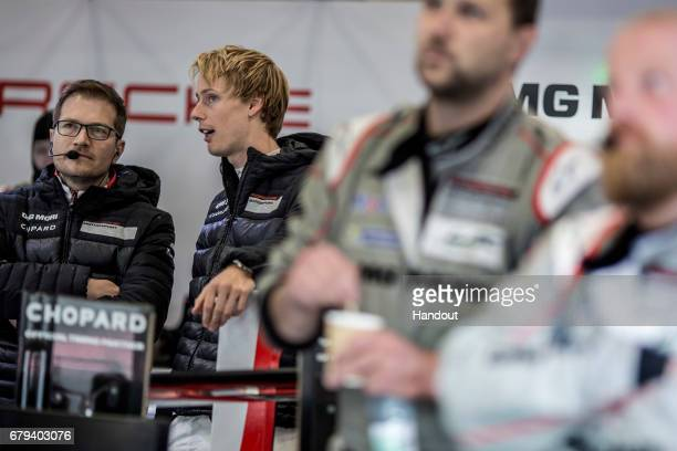 In this handout image provided by Red Bull #2 Porsche LMP1 driver Brendon Hartley of New Zealand talks with Team Principal Andreas Seidl of Germany...