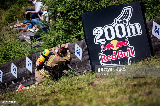 In this handout image provided by Red Bull A fireman competitor reacts on his way up the 400 metre long ski jump course with 140 metres of elevation...