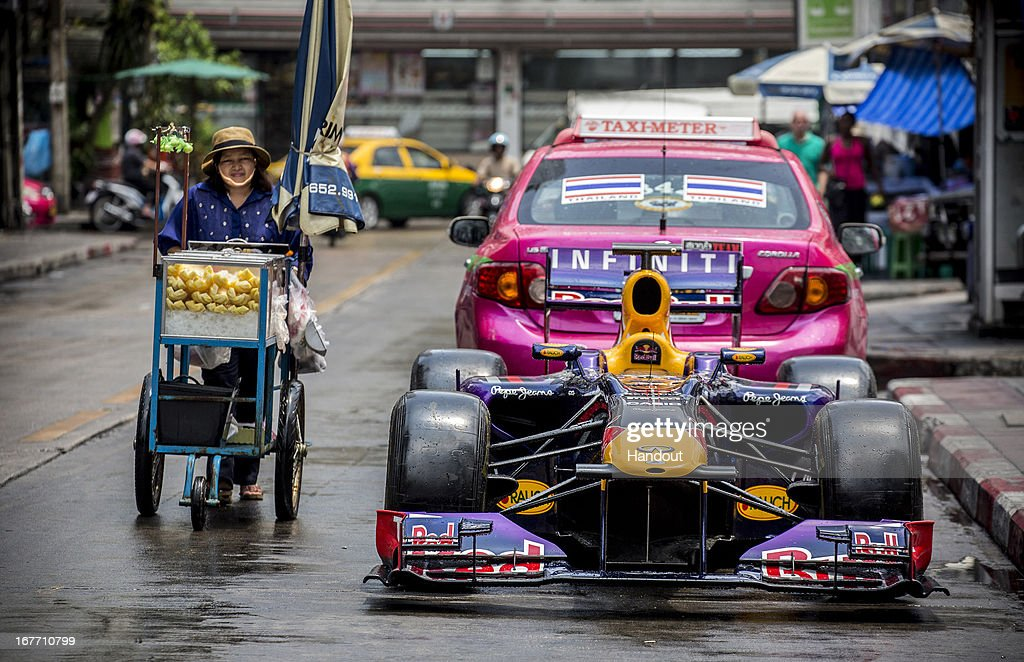 In this handout image provided by Red Bull, A food vendor pushes her cart past a Red Bull Racing RB6 Formula 1 car parked on the street in Sukhumvit 11 as European Red Bull begins of week of activities to launch it's brand in Thailand, on April 28, 2013 at Bangkok, Thailand.