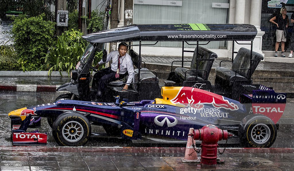 In this handout image provided by Red Bull, A tuk-tuk driver stops to look at a Red Bull Racing RB6 Formula 1 car parked on the street in Sukhumvit 11 as European Red Bull begins of week of activities to launch it's brand in Thailand, on April 28, 2013 at Bangkok, Thailand.