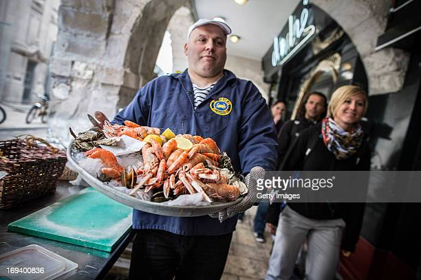 In this handout image provided by Red Bull a worker prepares a tray of seafood outside Chez Andre restaurant during the first stop of the Red Bull...