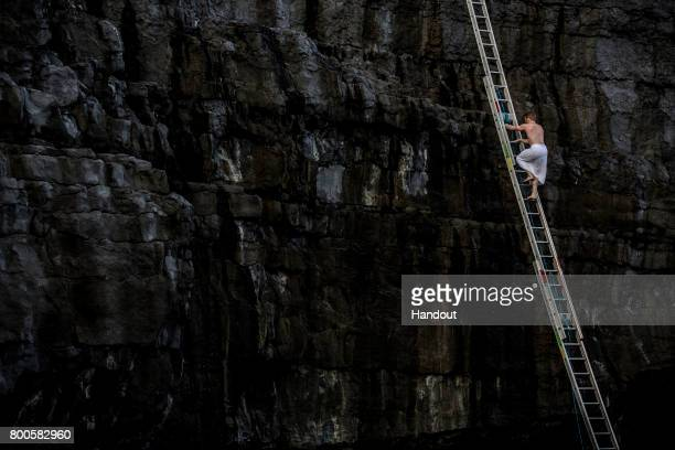 In this handout image provided by Red Bull Alain Kohl of Luxembourg climbs one of the ladders to the top of the cliff after diving from the 275 metre...