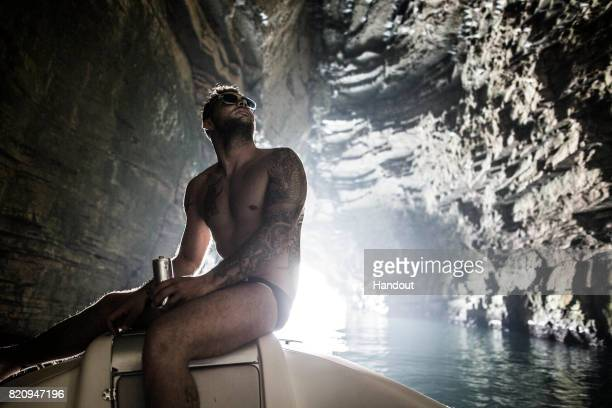 In this handout image provided by Red Bull Alessandro De Rose of Italy inspects the inside of Grotta dei Pipistrelli on his 'Road to Polignano' trip...