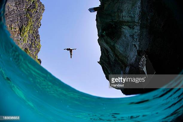 In this handout image provided by Red Bull Artem Silchenko of Russia dives from the 27 metre platform at Maya Bay in the Andaman Sea during the final...