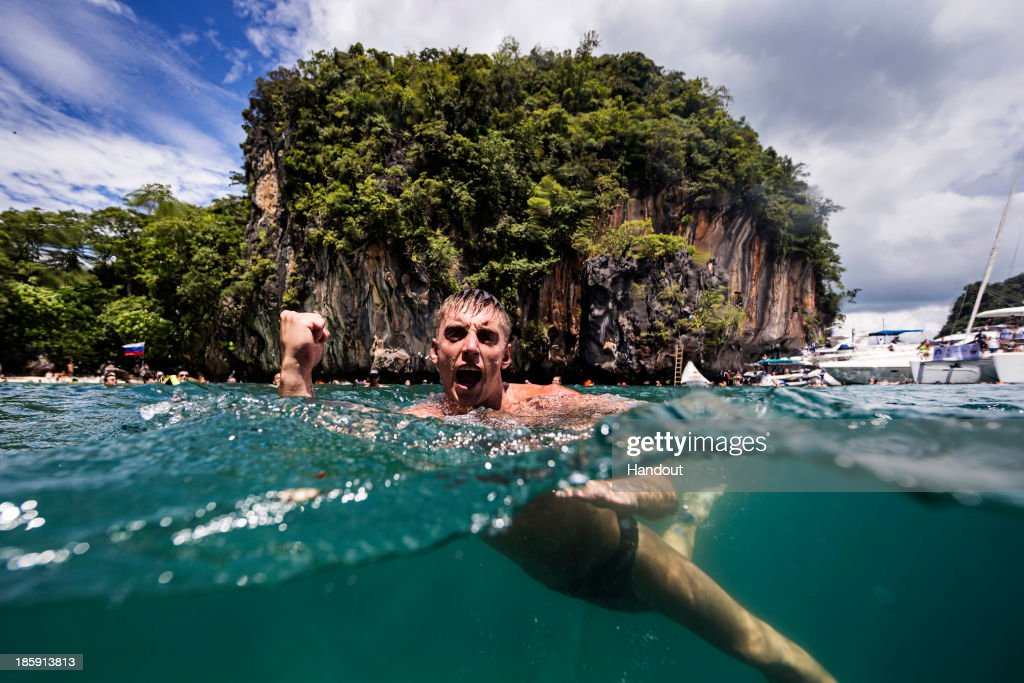 In this handout image provided by Red Bull, Artem Silchenko of Russia celebrates after his final dive from the 27 metre platform on Hong Island in the Andaman Sea during the last competition day of the eighth and final stop of the 2013 Red Bull Cliff Diving World Series on October 26, 2013 at Krabi, Thailand.