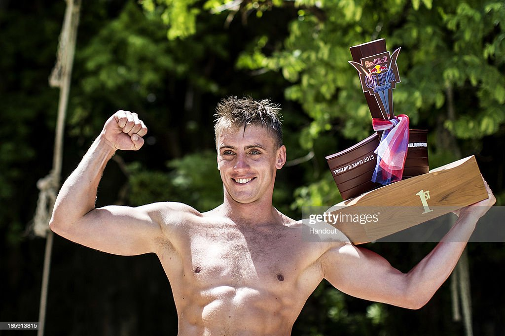 In this handout image provided by Red Bull, Artem Silchenko of Russia celebrates on the podium with the event trophy on Hong Island in the Andaman Sea during the last competition day of the eighth and final stop of the 2013 Red Bull Cliff Diving World Series on October 26, 2013 at Krabi, Thailand.