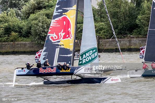 In this handout image provided by Red Bull Austria's Red Bull Sailing Team helmsman Roman Hagara of Austria slips off the boat as they compete in...