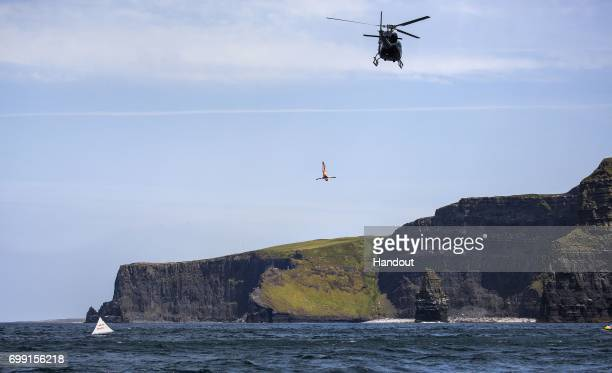 In this handout image provided by Red Bull Blake Aldridge of the UK dives 25 metres from a helicopter at the Cliffs of Moher in buildup to the first...