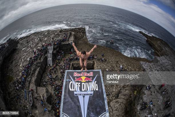 In this handout image provided by Red Bull Blake Aldridge of the UK dives from the 275 metre platform at the Serpent`s Lair during the first stop of...