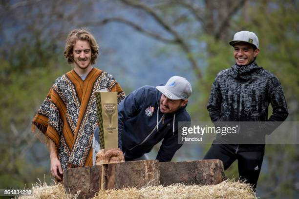 In this handout image provided by Red Bull Blake Aldridge of the UK reads the names of past winners on the King Kahekili Trophy while six times...