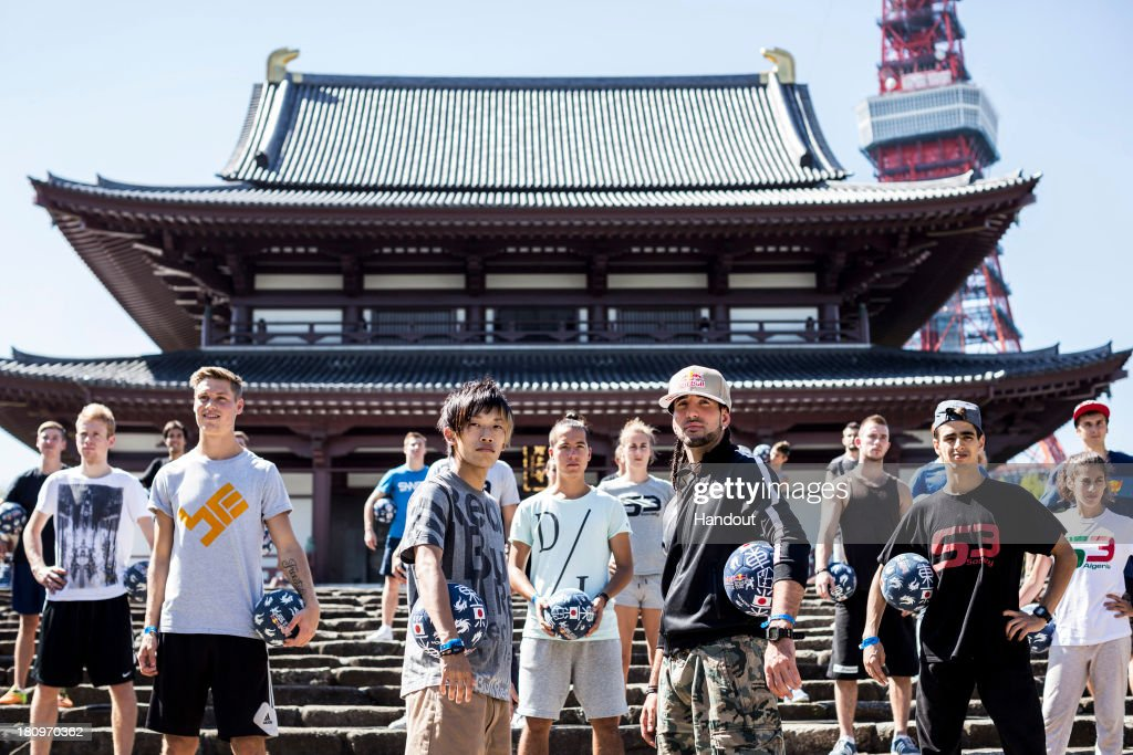 In this handout image provided by Red Bull, Current Street Style world champion, Kotaru Tokuda (front L) of Japan and former champion Sean Garnier (front R) of France in front of the Zojoji Temple with the other athletes in preparation for the Red Bull Street Style freestyle football world finals on September 17, 2013 in Tokyo, Japan.