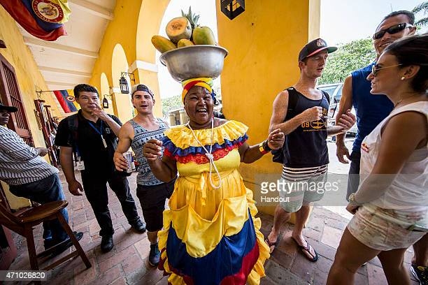 In this handout image provided by Red Bull David Colturi of the USA dances with a local lady amid the tourist markets during a city tour prior to the...