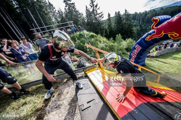In this handout image provided by Red Bull Firemen exchange the baton in a relay up the 400 metre long ski jump course with 140 metres of elevation...
