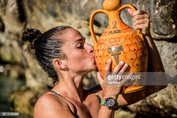 In this handout image provided by Red Bull Jacqueline Valente of Brazil celebrates with her trophy during the third stop of the Red Bull Cliff Diving...
