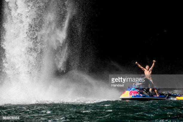 In this handout image provided by Red Bull Jonathan Paredes of Mexico celebrates after diving from the 27 metre platform next to Rininahue waterfall...