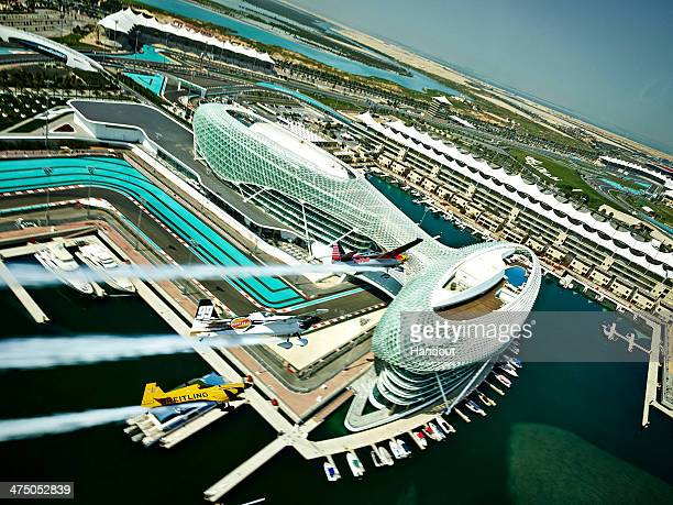 In this handout image provided by Red Bull Kirby Chambliss Michael Goulian of the United States and Nigel Lamb of Great Britain fly over the Yas...