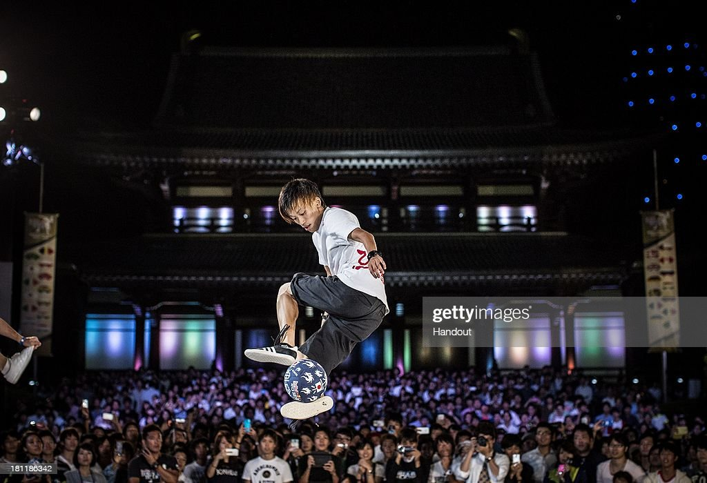 In this handout image provided by Red Bull, Kotaro Tokuda of Japan competes at Zojoji Temple during the Red Bull Street Style freestyle football world finals on September 19, 2013 at Tokyo, Japan.