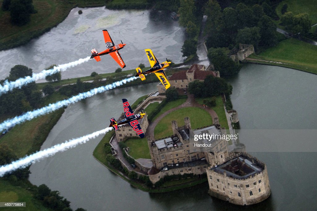 In this handout image provided by Red Bull, Matt Hall of Australia and Nicolas Ivanoff of France fly in formation with Kirby Chambliss of the United States prior to the fifth stage of the Red Bull Air Race World Championship in front of the Leeds Castle on August 14, 2014 in Kent, United Kingdom.