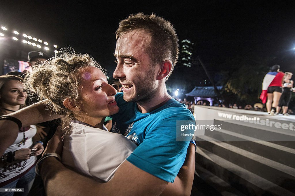 In this handout image provided by Red Bull, men's winner, Szymon Skalski (C) of Poland celebrates with women's winner, Kitti Szasz (L) of Hungary at Zojoji Temple during the Red Bull Street Style freestyle football world finals on September 19, 2013 at Tokyo, Japan.