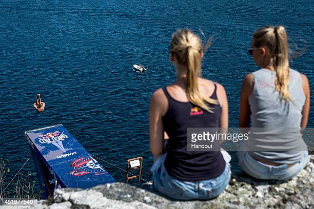 In this handout image provided by Red Bull Michal Navratil of the Czech Republic dives from the 275 metre platform as two local girls watch on during...