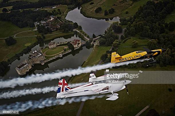 In this handout image provided by Red Bull Nigel Lamb and Paul Bonhomme of Great Britain fly in formation with Matthias Dolderer of Germany prior to...