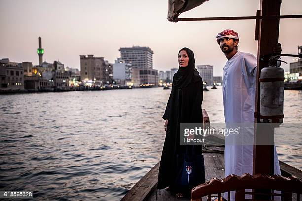 In this handout image provided by Red Bull Orlando Duque of Colombia and Helena Merten of Australia ride across Dubai Creek on an abra water taxi...