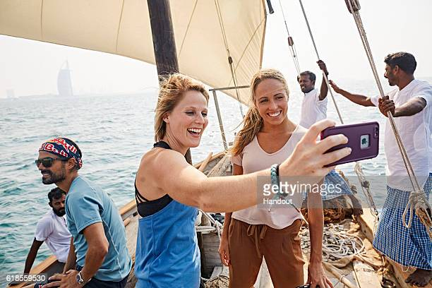 In this handout image provided by Red Bull Rachelle Simpson of the USA and Helena Merten of Australia take a selfie while sailing on a traditional...