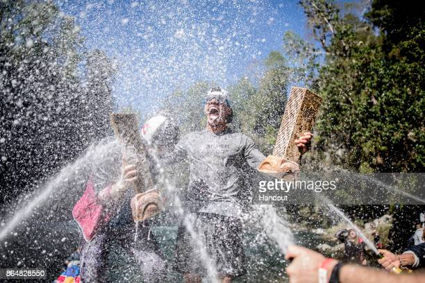 In this handout image provided by Red Bull Rhiannan Iffland of Australia and Jonathan Paredes of Mexico are sprayed with champagne after winning...