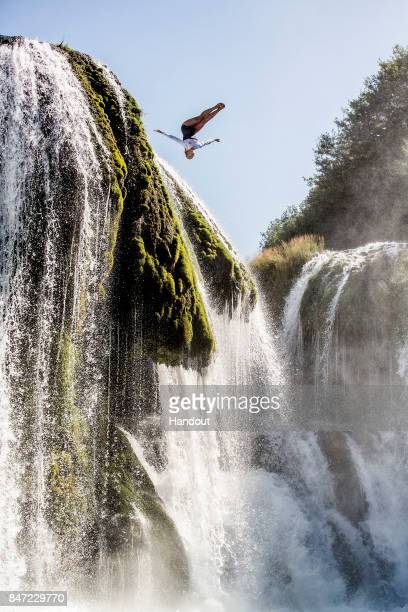 In this handout image provided by Red Bull Rhiannan Iffland of Australia dives from Strbacki waterfall at Una National Park during a road trip to...