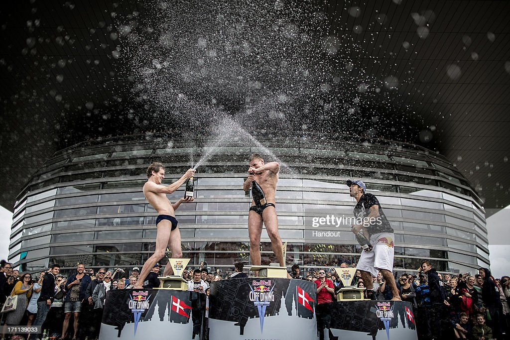 In this handout image provided by Red Bull, second placed Gary Hunt (L) of the UK, event winner Artem Silchenko (C) of Russia and third placed Orlando Duque (R) of Colombia celebrate on the podium in front of the Copenhagen Opera House during the second stop of the Red Bull Cliff Diving World Series on June 22, 2013 at Copenhagen, Denmark.