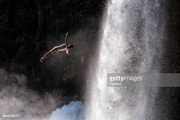 In this handout image provided by Red Bull Sergio Guzman of Mexico dives from the 27 metre platform next to Rininahue waterfall during the sixth and...
