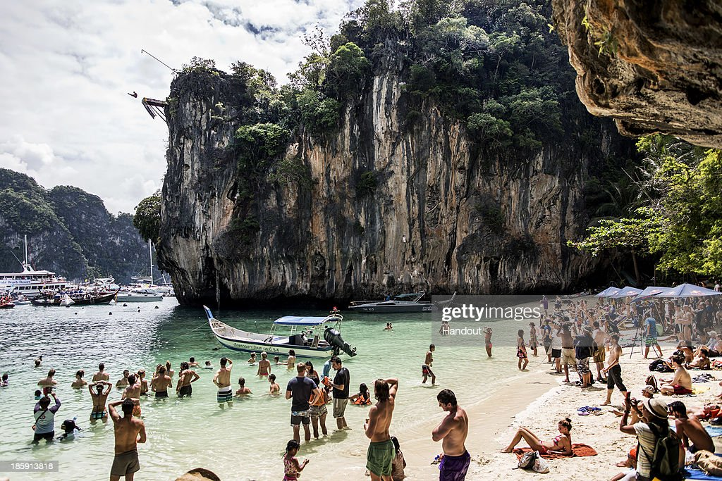 In this handout image provided by Red Bull, Spectators watch on as Kent De Mond of the USA dives from the 27 metre platform on Hong Island in the Andaman Sea during the last competition day of the eighth and final stop of the 2013 Red Bull Cliff Diving World Series on October 26, 2013 at Krabi, Thailand.
