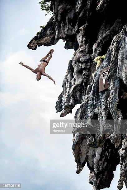 In this handout image provided by Red Bull Steven LoBue of the USA dives from a 25 metre rock at Viking Caves in the Andaman Sea during competition...