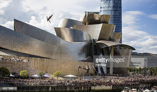In this handout image provided by Red Bull Steven LoBue of the USA dives from the 27 metre platform on La Salves Bridge next to the Guggenheim Museum...