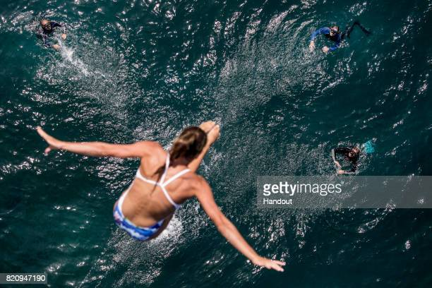 In this handout image provided by Red Bull The safety divers watch as Helena Merten of Australia dives from the 21 metre platform during the first...