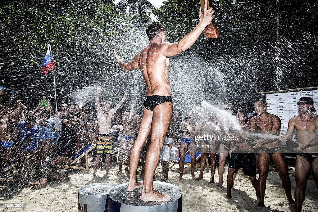 In this handout image provided by Red Bull, World Series Champion Artem Silchenko (C) of Russia celebrates on the podium as the other divers spray him with champagne on Hong Island in the Andaman Sea during the last competition day of the eighth and final stop of the 2013 Red Bull Cliff Diving World Series on October 26, 2013 at Krabi, Thailand.