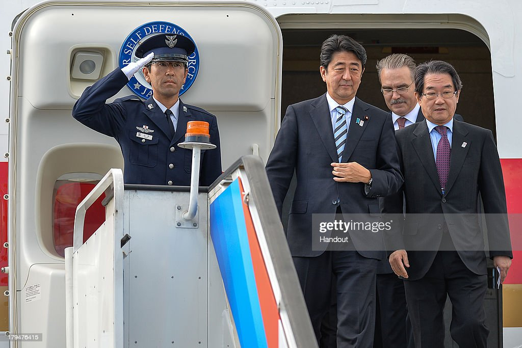 In this handout image provided by Ria Novosti, Japanese Prime Minister Shinzo Abe (C) arrives ahead of the G20 summit on September 4, 2013 in St. Petersburg, Russia. World leaders are arriving in Russia ahead of the start of the G20 summit which is scheluded to run between September 5th and 6th.