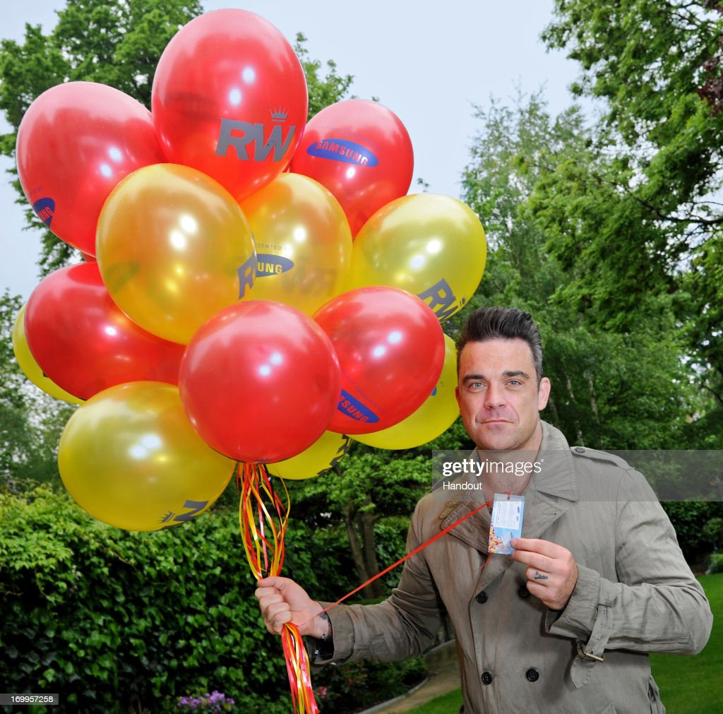 In this handout image provided by Samsung, <a gi-track='captionPersonalityLinkClicked' href=/galleries/search?phrase=Robbie+Williams&family=editorial&specificpeople=201201 ng-click='$event.stopPropagation()'>Robbie Williams</a> and Samsung get set to celebrate his upcoming Take The Crown Stadium Tour 2013 which starts next week by releasing 1,000 balloons at a secret location in London tomorrow on June 5, 2013 in London, England. Twenty of the balloons will have lucky winning tickets attached to either a pair of tickets to one of his London concerts or a Samsung Galaxy Camera.