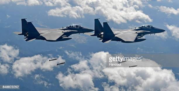 In this handout image provided by South Korean Defense Ministry South Korean Air Force F15K fighter jets drop MK82 bomb during a training at the...