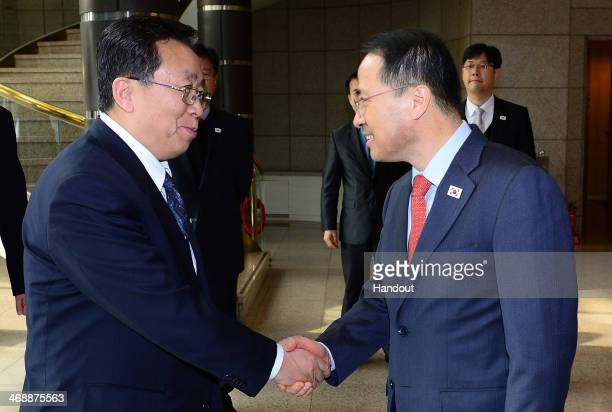 In this handout image provided by South Korean Unification Ministry Kim KyouHyun the head of South Korea's highlevel delegation shakes hands with his...