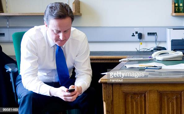 In this handout image provided by the Conservative Party Leader of the Conservative Party David Cameron texts on his mobile phone as he waits for...