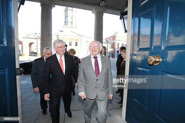 In this handout image provided by the Dept of the Taoiseach President of Ireland Michael D Higgins is greeted by Tanaiste Eamon Gilmore at the Hunger...