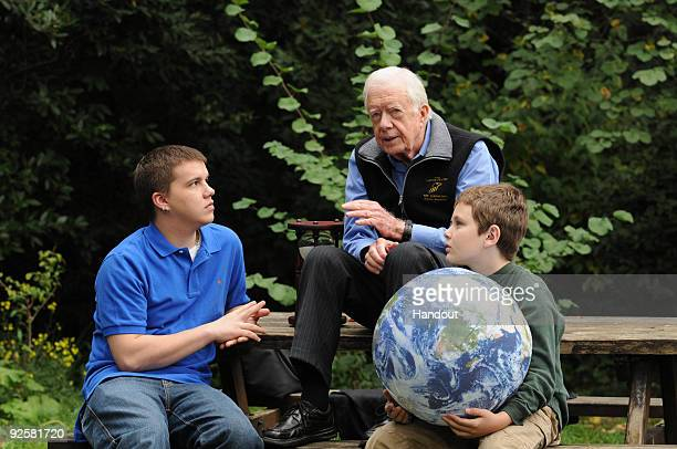 In this handout image provided by the Elders Jimmy Carter walks with his grandsons Jeremy Carter and Hugo Wentzel 10 during a picnic event on October...